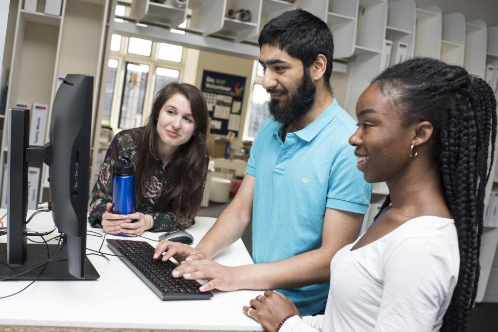 three students looking at pc